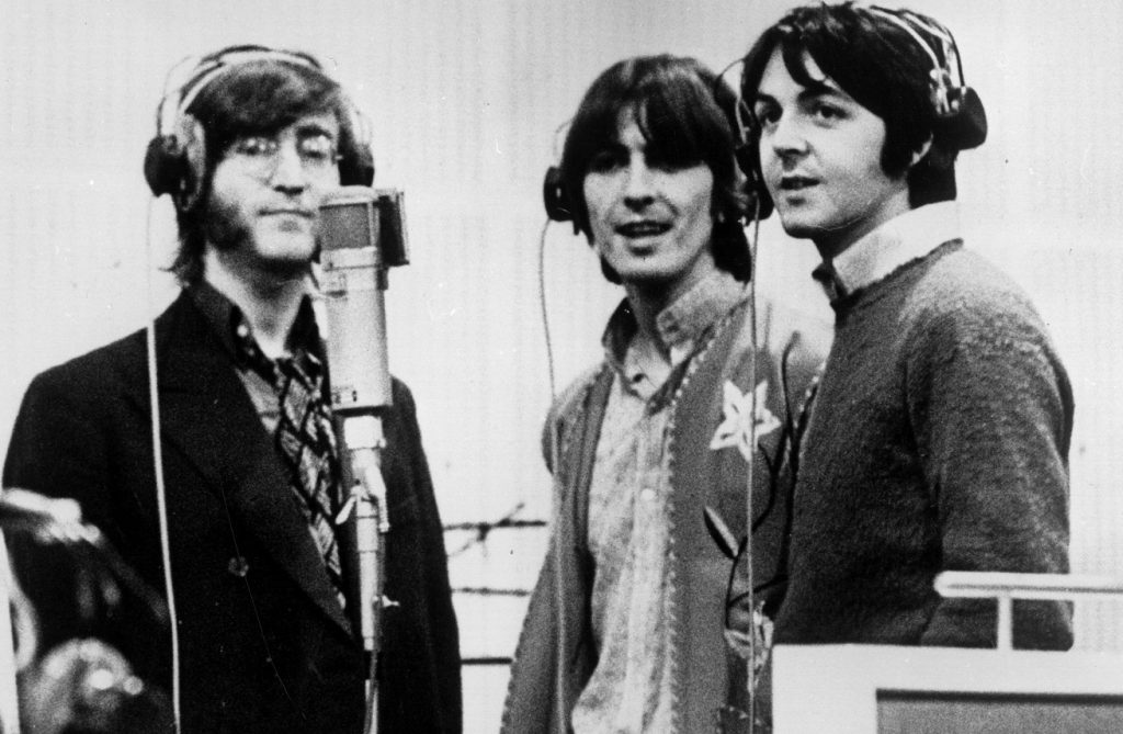 John Lennon, George Harrison. and Paul McCartney standing at a microphone