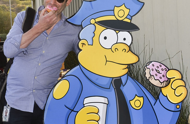 'Simpsons' character Chief Wiggum stands with a donut