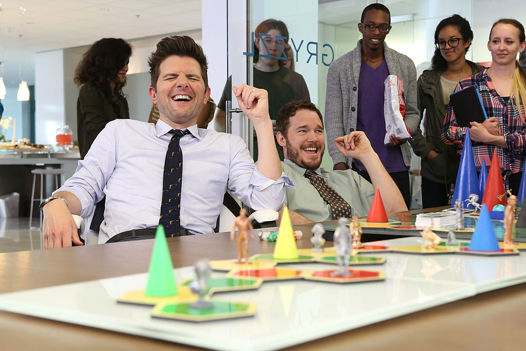 """Ben Wyatt (Adam Scott) and Andy Dwyer (Chris Pratt) play Cones of Dunshire at Gryzzl in Season 6, Episode 21, """"Moving Up"""" of 'Parks and Recreation.'"""