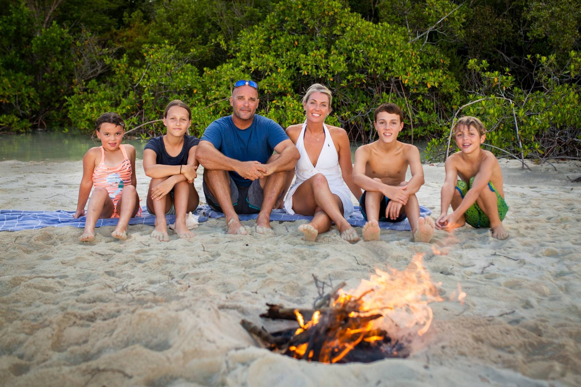Renovation Island stars Sarah and Bryan Baeumler and their children sitting on the sand in front of a fire