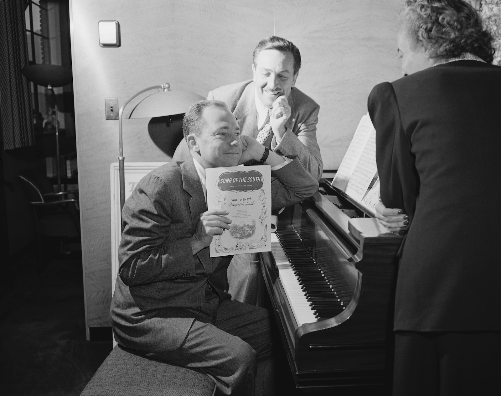 Walt Disney watched musician Johnny Mercer at the piano, as he holds up the sheet music from Disney's 'Song of the South' movie, October 28, 1946.