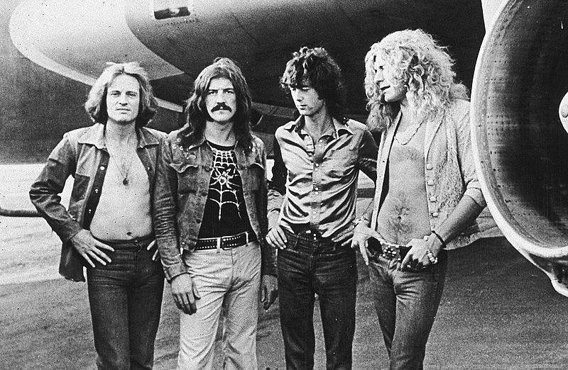 Led Zeppelin posed in front of the band airplane