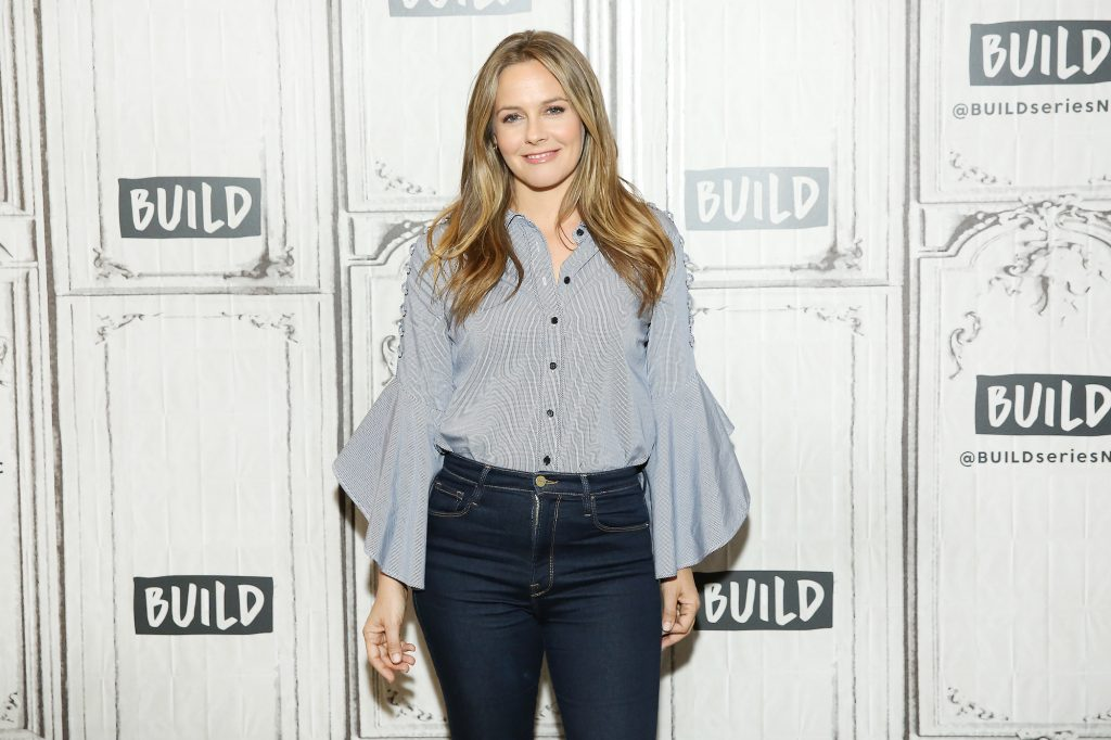 Alicia Silverstone smiling in front of a white and gray background