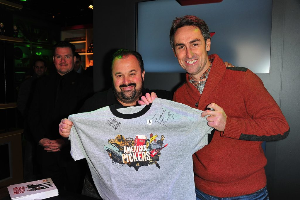 (L-R) Frank Fritz and Mike Wolfe from American Pickers holding up an autographed shirt and smiling