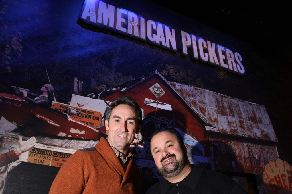 Mike Wolfe and Frank Fritz smiling in front of an American Pickers logo