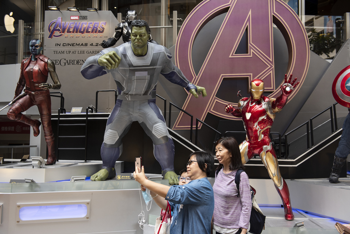 Pedestrians take a selfie with Marvel figures