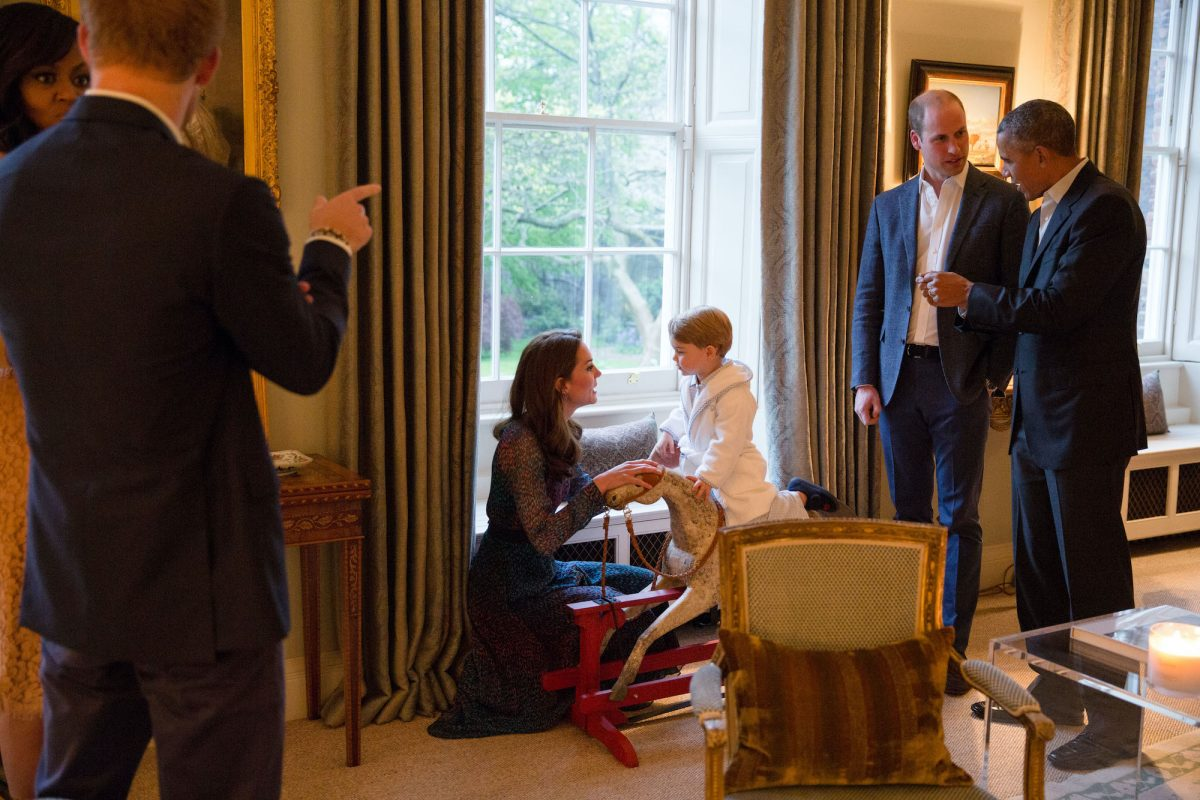 Barack Obama talks with Prince William as Kate Middleton plays with Prince George as Michelle Obama talks with Prince Harry