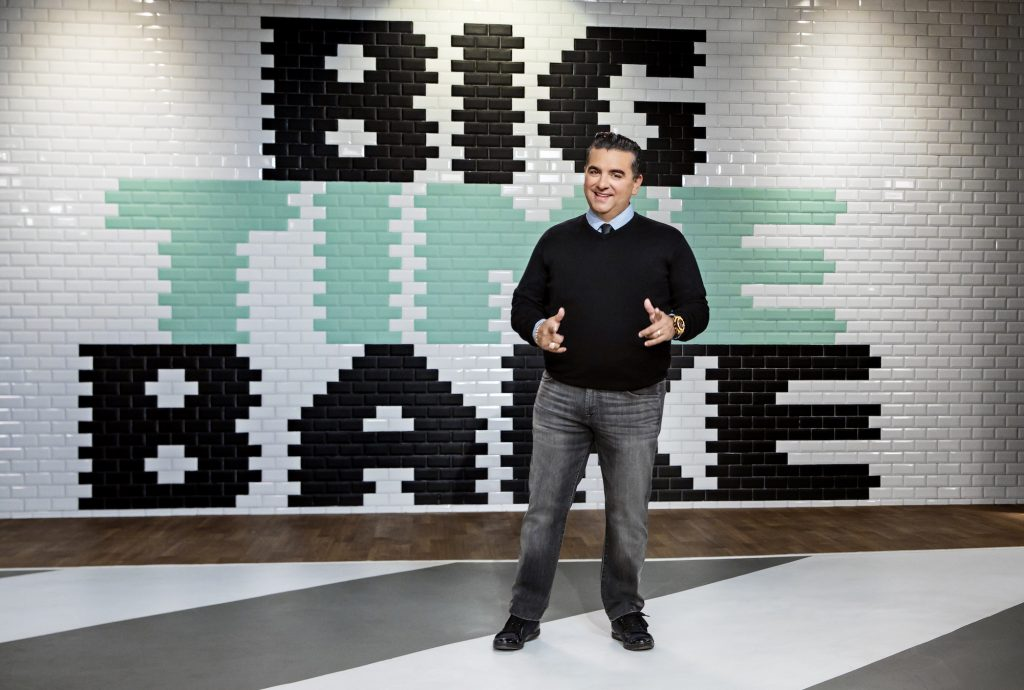 Buddy Valastro in front of a tile wall with the 'Big Time Bake' logo