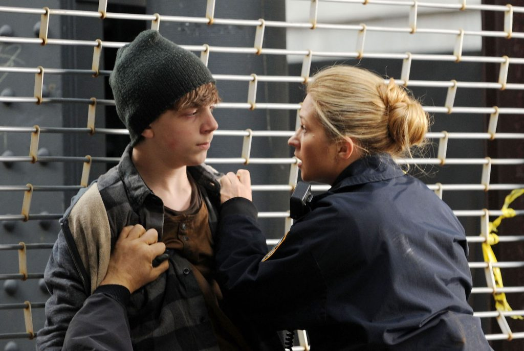 Gabriel Rush held up against a metal fence by Vanessa Ray on set of Blue Bloods