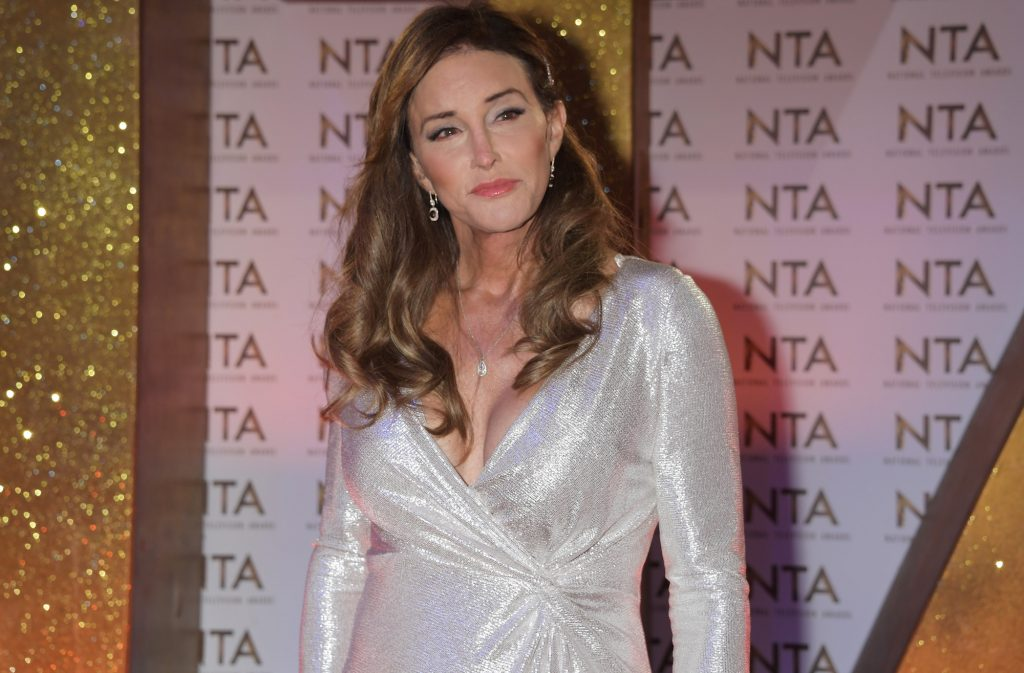 Caitlyn Jenner looking to the side, smiling, wearing a silver dress