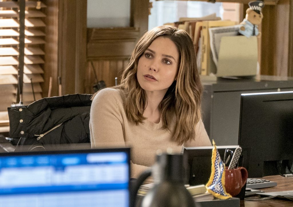 Sophia Bush as Erin Lindsay sitting at a desk, looking to the side
