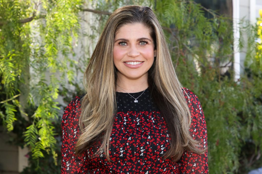 Danielle Fishel smiling looking at the camera in front of a tree