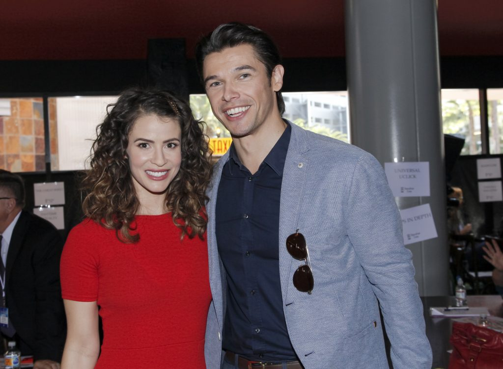 Linsey Godfrey and Paul Telfer smiling, looking at the camera