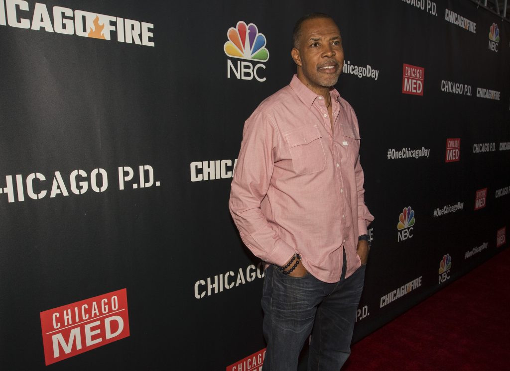 Eriq La Salle smiling, turned into the side, in front of a dark background with repeating 'Chicago' logos
