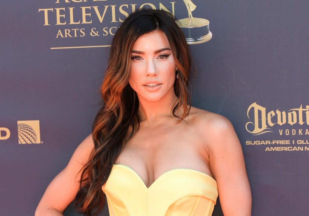 Jacqueline MacInnes Wood looking at the camera in front of a dark blue background