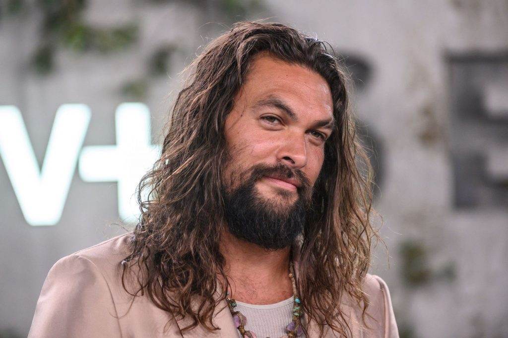 Jason Momoa smiling at the camera in front of a tan background