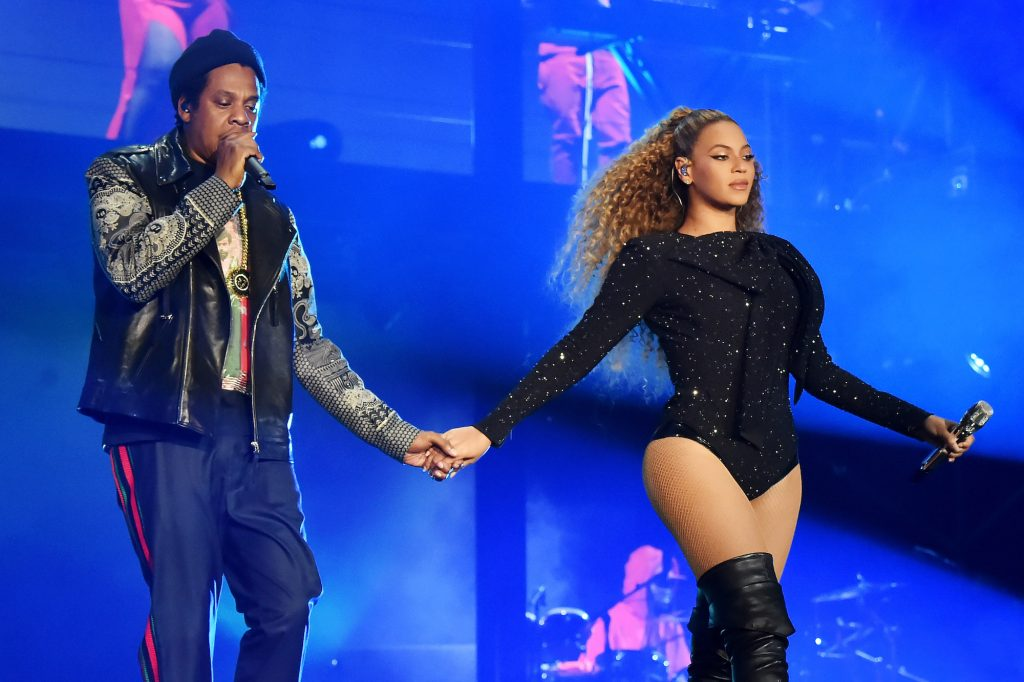 Jay-Z and Beyoncé holding hands on stage