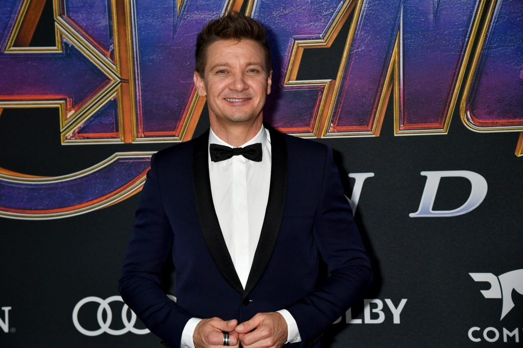 Jeremy Renner smiling wearing a suit and bow tie