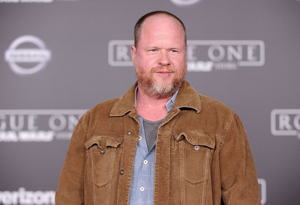 Joss Whedon looking away from the camera in front of a gray background