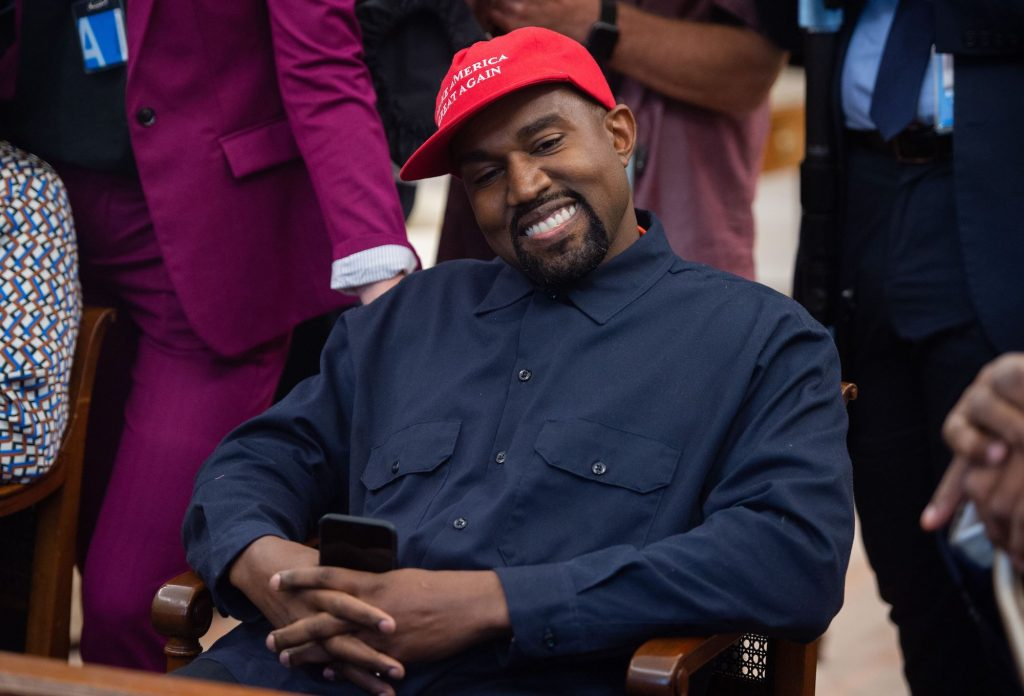 Kanye West smiling looking away from the camera wearing a red hat that says 'Make America Great Again'