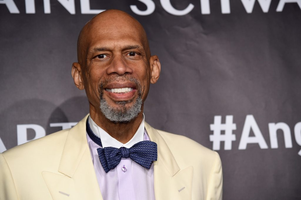 Kareem Abdul-Jabbar smiling in front of a black background wearing a white suit and blue bowtie