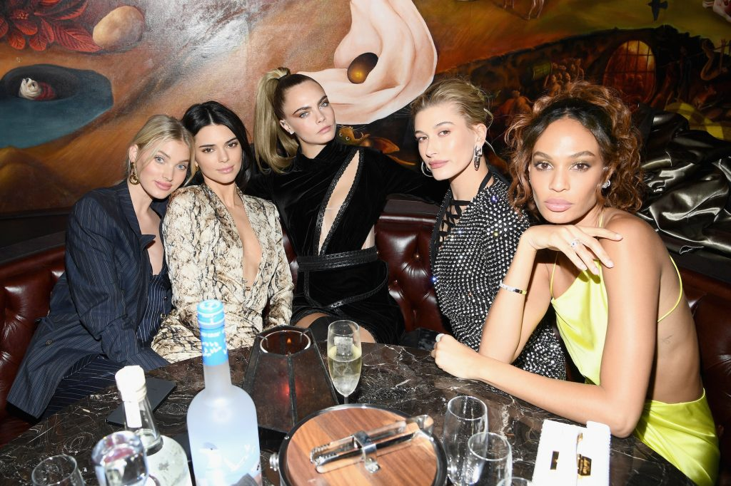 (L-R) Elsa Hosk, Kendall Jenner, Cara Delevingne, Hailey Bieber, and Joan Smalls sitting in a booth at a restaurant