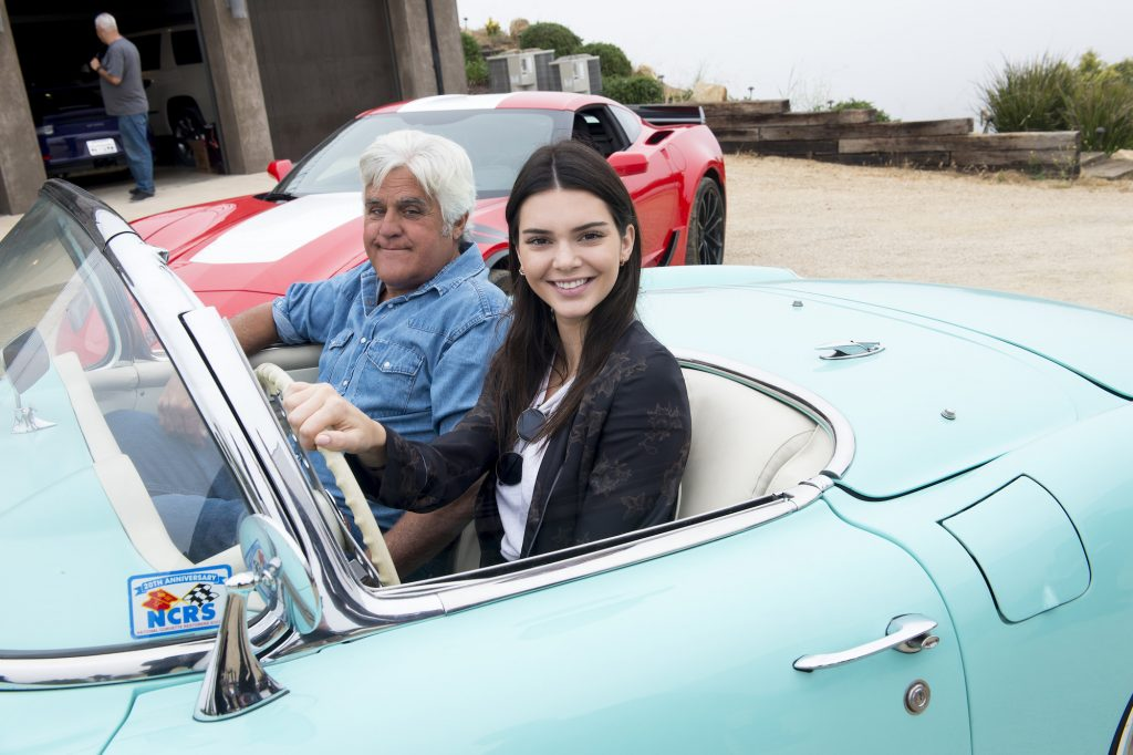 (L-R) Jay Leno and Kendall Jenner smiling sitting in a blue convertible