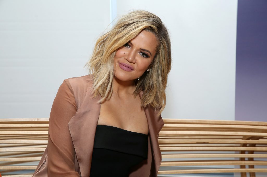 Khloé Kardashian smiling in front of a white background