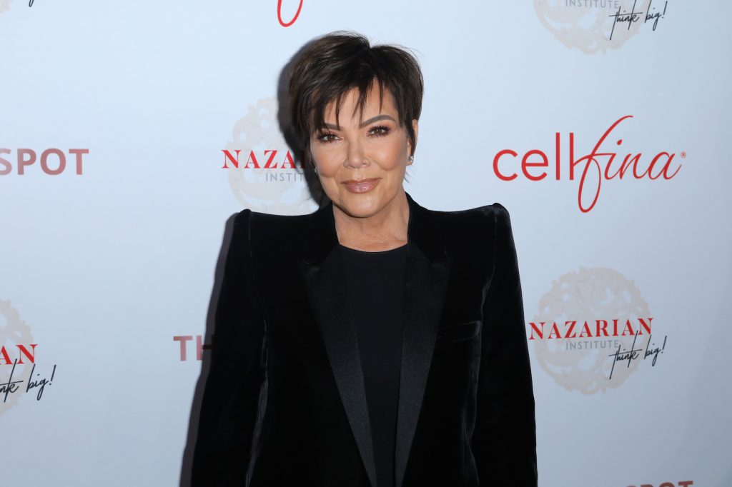 Kris Jenner smiling in front of a white background