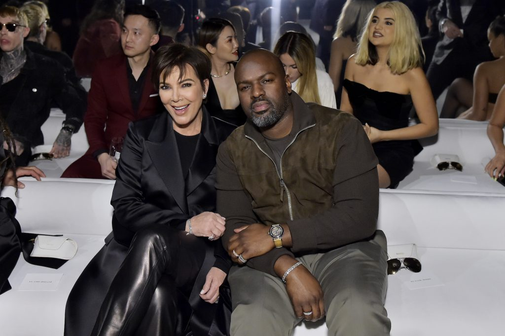 Kris Jenner and Corey Gamble smiling in the front row of a fashion show