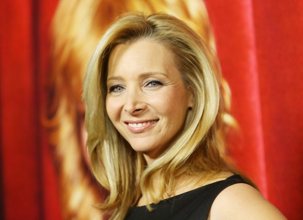 Lisa Kudrow smiling in front of a red background