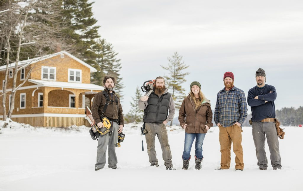 Cast of Maine Cabin Masters in a field covered in snow