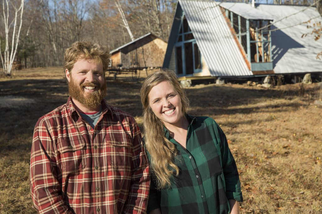 Chase and Ashley Morrill smiling in front of an A-frame house
