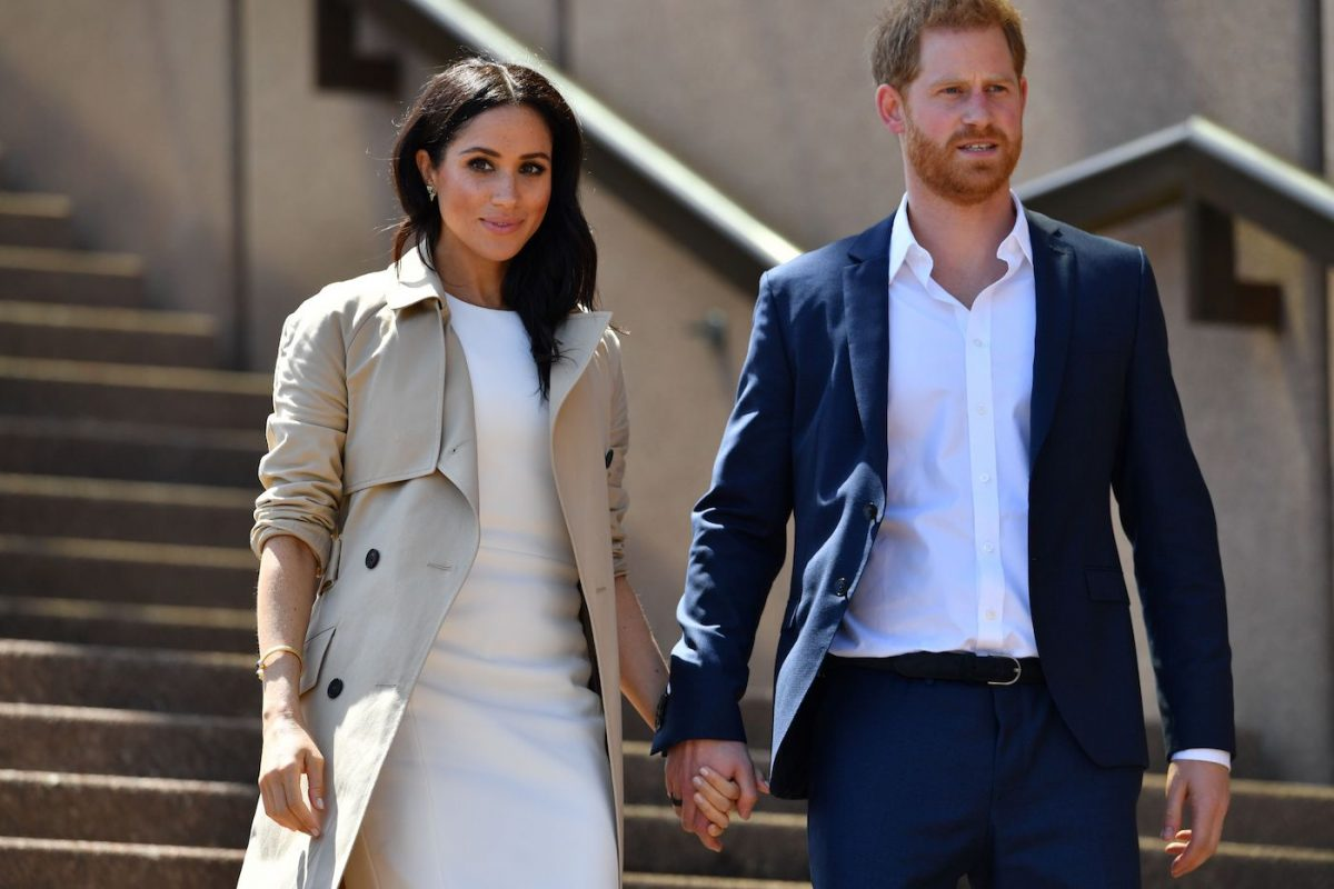 Meghan Markle and Prince Harry hold hands walking down the steps of the Sydney Opera House