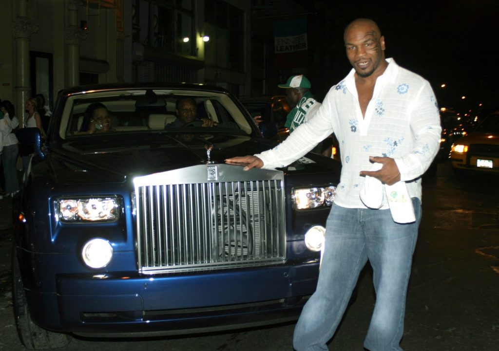 Mike Tyson posing next to a car