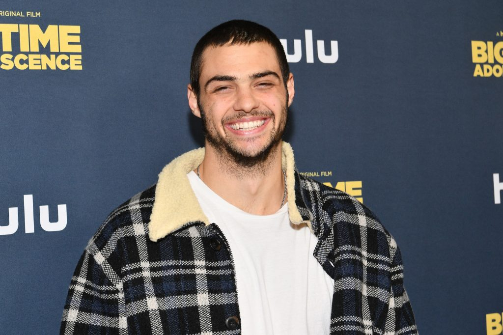 Noah Centineo smiling in front of a navy blue background