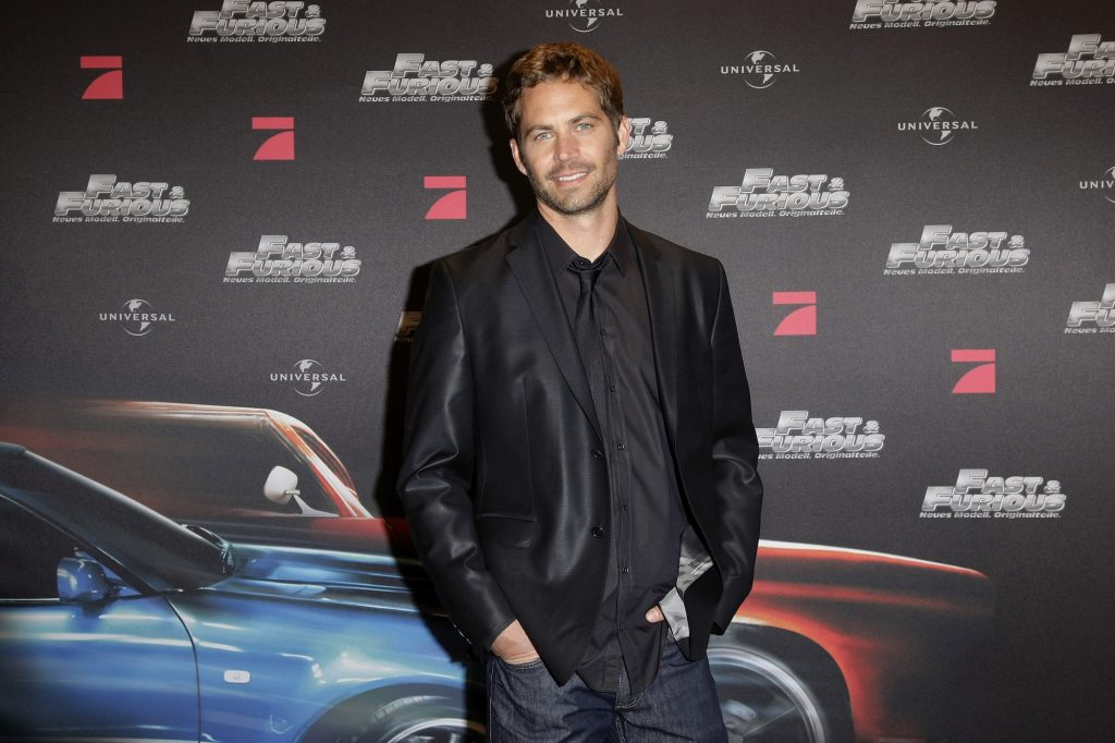 Paul Walker smiling at the camera in front of a dark background with repeating 'Fast and Furious' logos