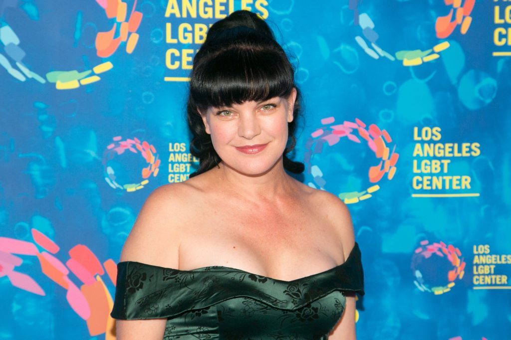 Pauley Perrette smiling in front of a blue background