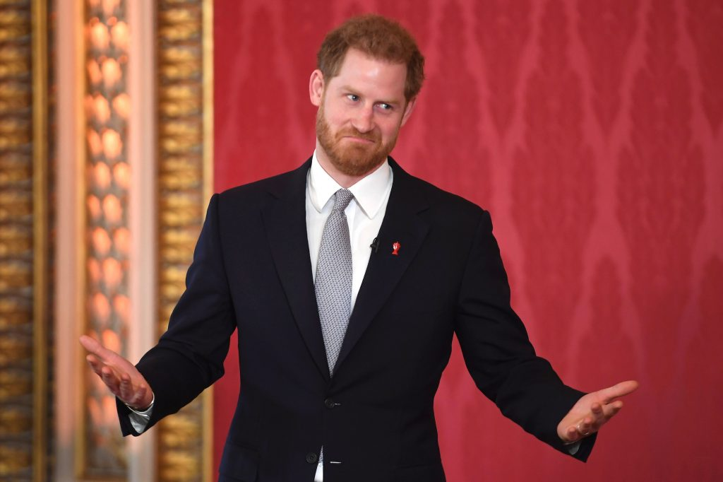 Prince Harry shrugging and smiling in front of a red background