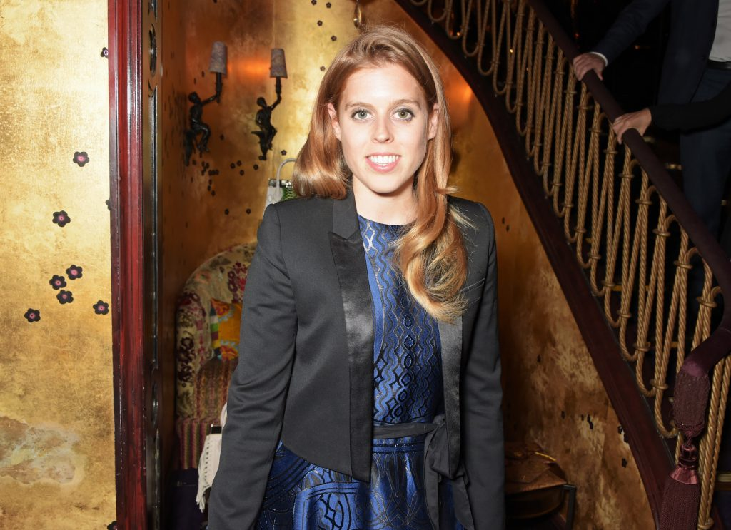 Princess Beatrice smiling at the camera standing next to a staircase
