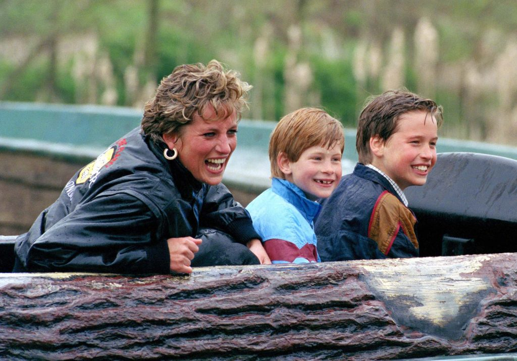 Princess Diana, Prince William, and Prince Harry laughing, wet from rain