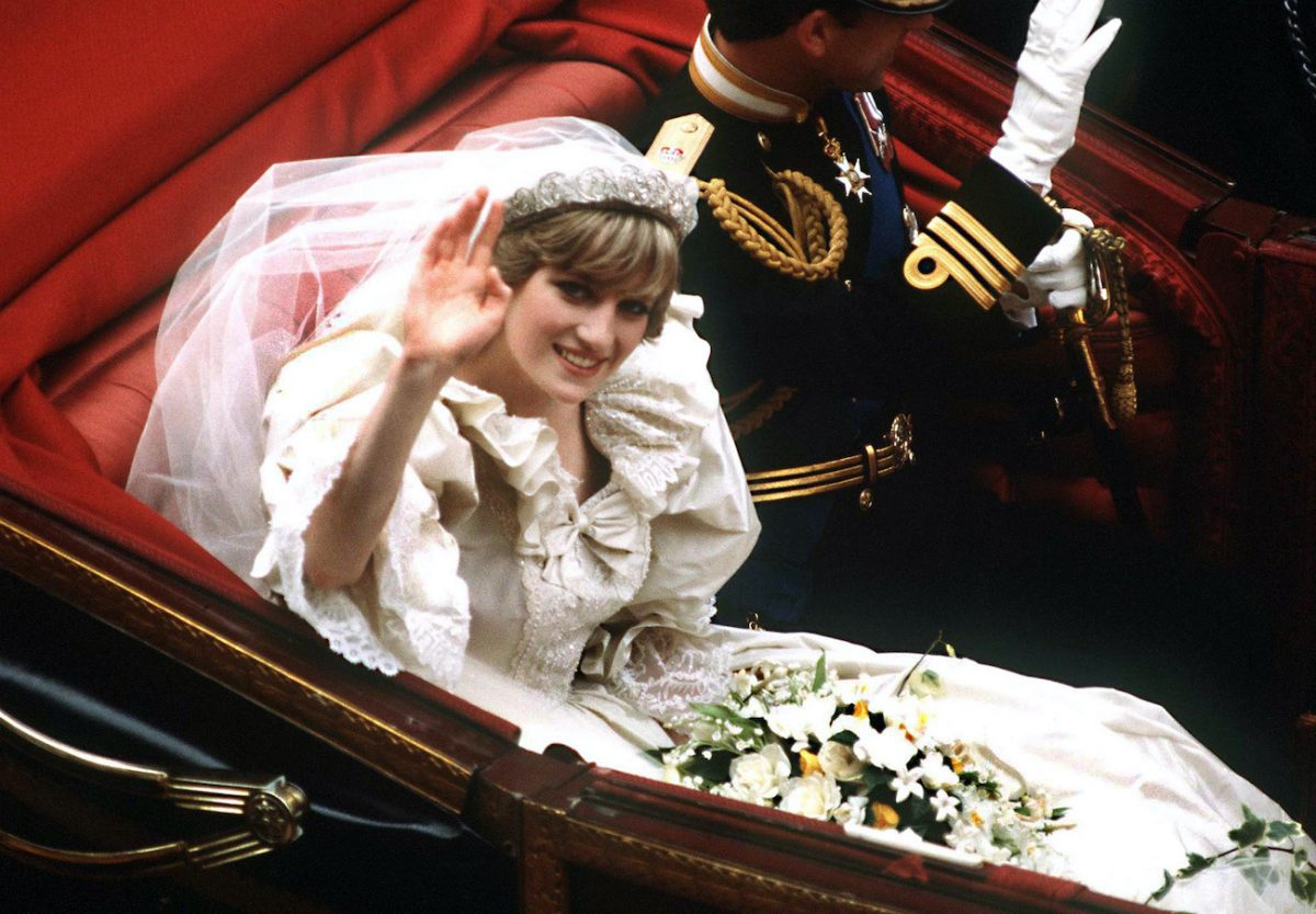 Princess Diana and Prince Charles wave while riding in a carriage during their royal wedding