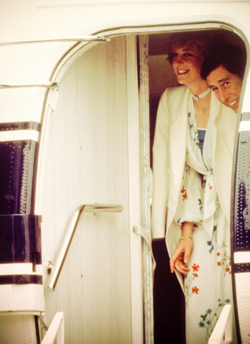 Princess Diana and Prince Charles smile as they board a plane to start their honeymoon