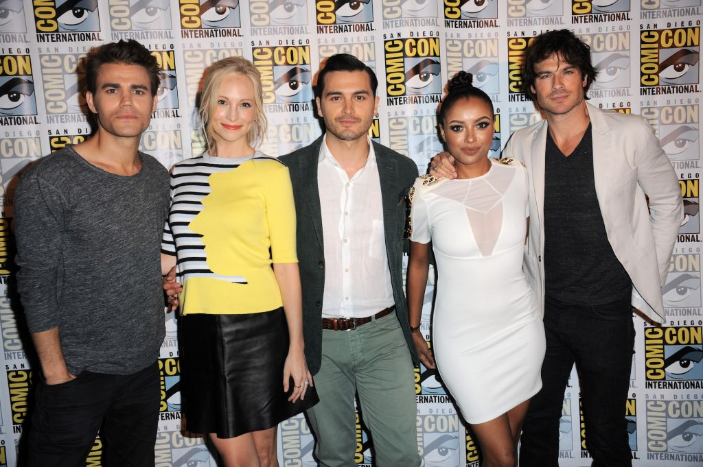 (L-R) Paul Wesley, Candice Accola, Michael Malarkey, Kat Graham and Ian Somerhalder smiling in front of a Comic Con backdrop