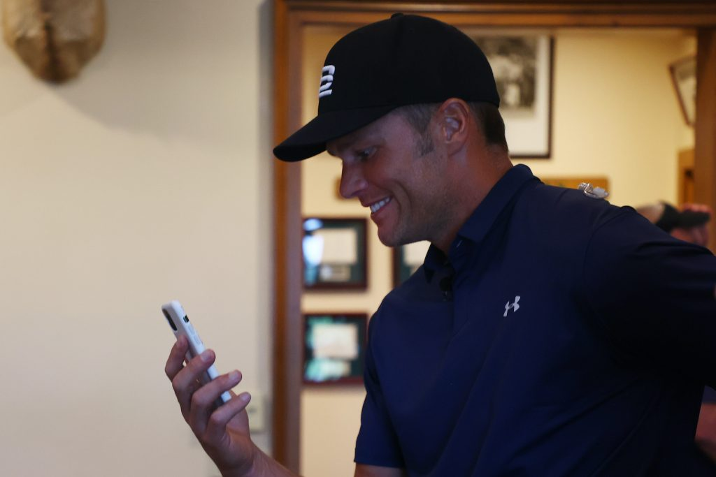 NFL player Tom Brady of the Tampa Bay Buccaneers waits out a weather delay in the clubhouse during The Match: Champions For Charity at Medalist Golf Club