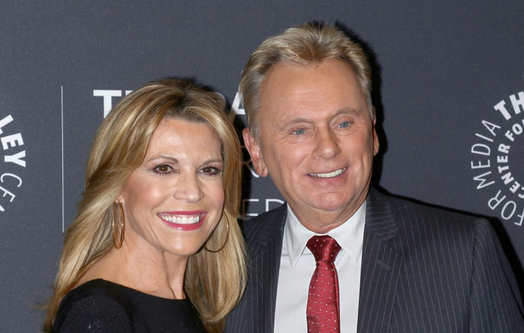 Vanna White and Pat Sajak smiling in front of a gray background