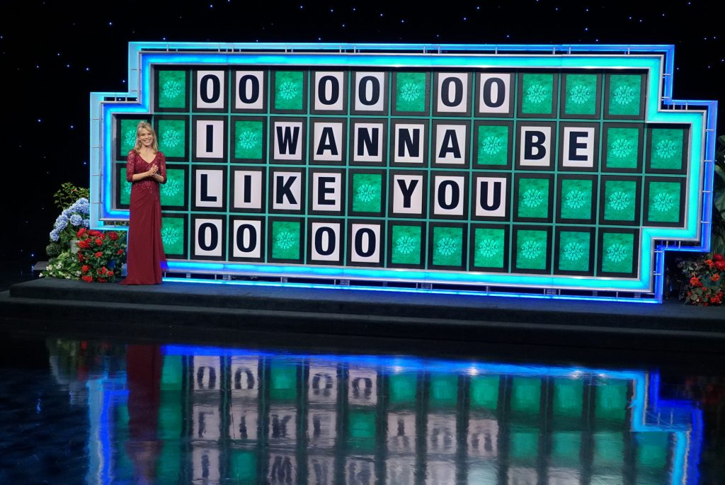 Vanna White smiling next to the Wheel of Fortune letterboard