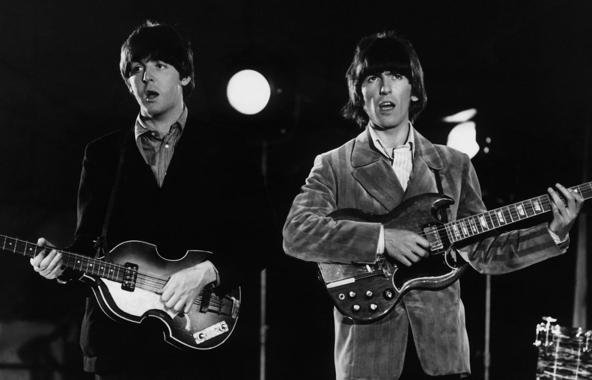 Beatles Paul and George playing their guitars on stage