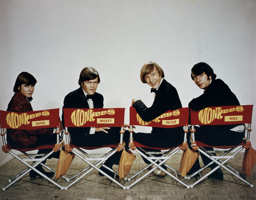 The Monkees sitting in chairs