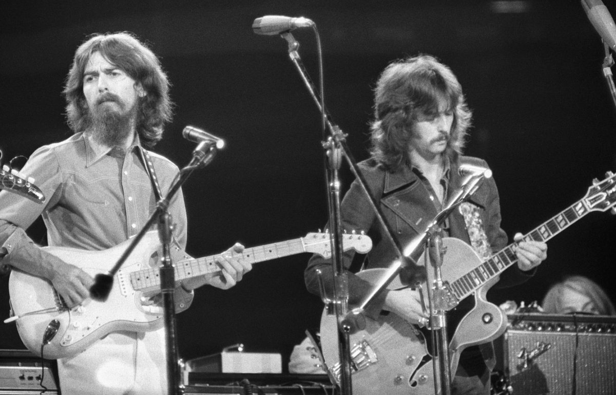 George Harrison and Eric Clapton play guitars onstage.